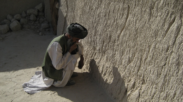 A villager waits while international soldiers search his compound for evidence of insurgent activity. Kandahar Province, Afghanistan. Photo © Frank Vilaca